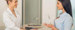 Kieferorthopädin spricht über Mundhygiene mit Patientin