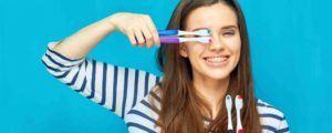 Frau hat Zahnbürsten in der Hand