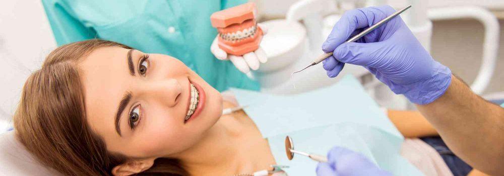 Patientin liegt im Zahnarztsessel Hand mit Hadachuh